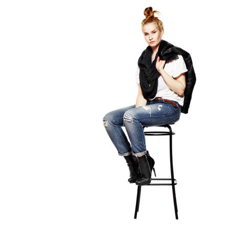 Young blonde woman sitting on high stool. Rock style. Isolated on white background. photo