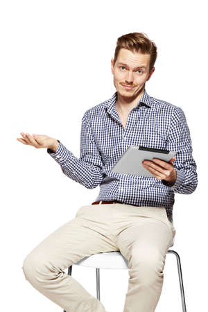 dissatisfaction: Disappointed young man holding tablet. Studio shot isolated on white.