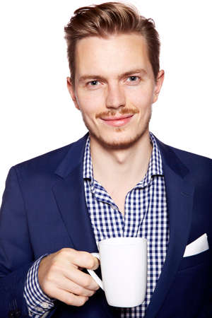 facial expression: Portrait of a handsome young man drinking coffee. Isolated on white background.