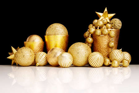 shiny christmas baubles: Gold Christmas decorations on black background.