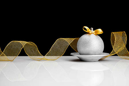 Silver Christmas ball with gold colored bow.