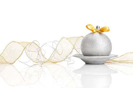 Silver Christmas ball with gold colored bow on white background.