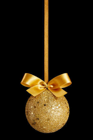 christmas deco: Gold Christmas ball with bow on black background Stock Photo