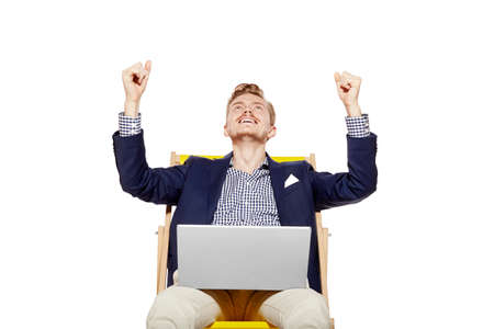 empleado de oficina: El estudio tir� de hombre joven feliz sentado en el ba�o de sol. �l levanta los brazos en un gesto de victoria. Foto de archivo