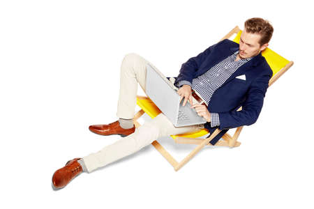 work shoes: Concept photo of young man lies on a sunbed and doing a business case. Isolated on white background.