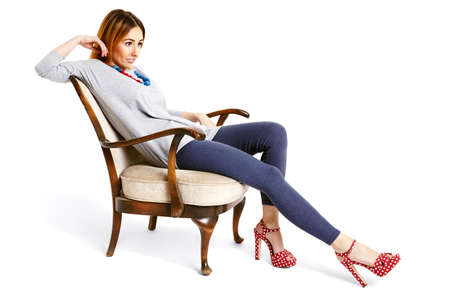 20 29: Young woman sitting on an old school chair with pulled leg relaxing and cheerfully smiling.