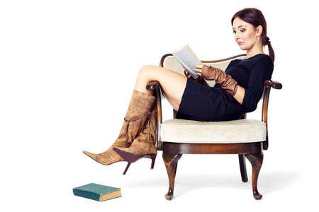 mujeres morenas: Mujer atractiva que lee un libro mientras está sentado cómodamente en una silla vieja.