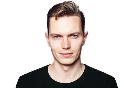 Young man looking at the camera. Isolated on white background. Horizontal format, he has a serious face, he is wearing a black T-shirt.