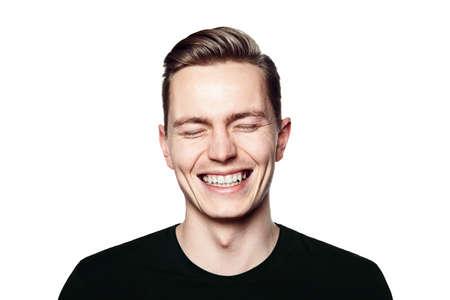 volto uomo: Lo studio ha sparato del giovane che sorride alla macchina fotografica. Isolato su sfondo bianco. Formato orizzontale, che sta cercando di telecamera, che indossa una maglietta nera.