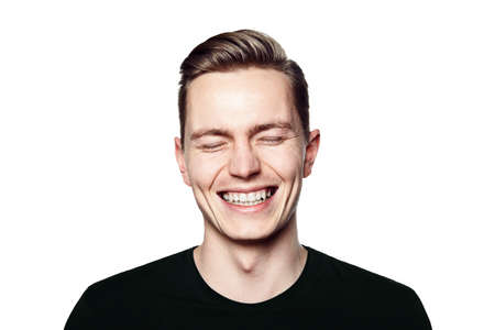 young man smiling: Studio shot of young man smiling to camera. Isolated on white background. Horizontal format, he is looking to the camera, he is wearing a black T-shirt.