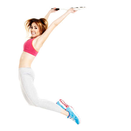 20 29: Sportswoman jumps up. Shes on her tennis training. Studio shot isolated on white background.
