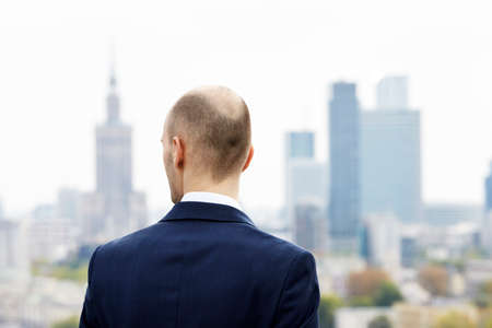 cityspace: Businessman standing on the roof and looking at downtown
