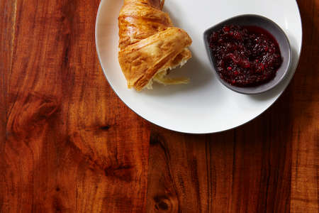 second breakfast: Croissants and jam for breakfast on wooden table. Copy space.