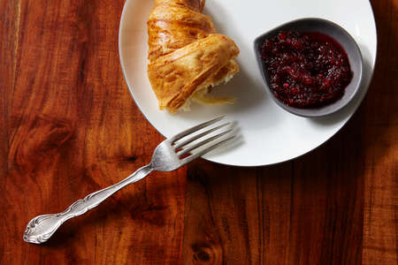 second breakfast: Croissants with jam for breakfast on dark wooden table. View from above.