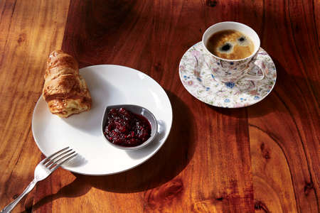 second breakfast: Croissants with jam and cup of hot coffee on wooden table.
