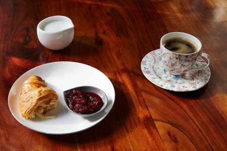 second breakfast: Croissants with jam and cup of coffee on wooden table.