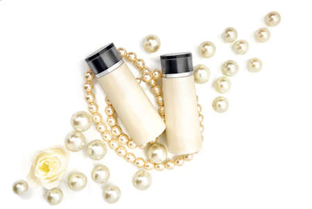 Two blank cosmetic bottles lying on pearls on a table. Studio shot on white background. Stock Photo