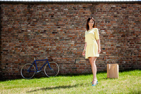 Attractive young woman in the park. She returns from shopping.