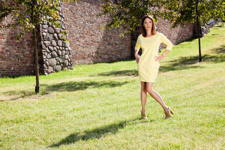 Attractive woman in yellow dress spends time in the park.