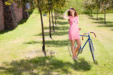 Beautiful young woman in pink dress and old style bike racing. Beautiful sunny day. Stock Photo