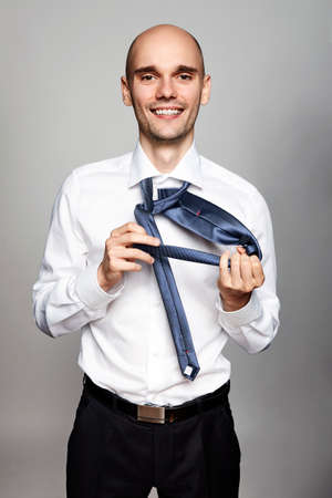 Studio shot of young businessman getting dressed. Portrait on gray background.