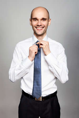 Portrait of smiling man in white shirt fixing his tie.  Stock Photo