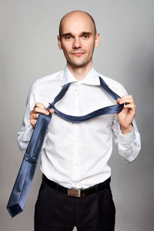 Studio shot of young businessman taking off a necktie. Portrait on gray background.