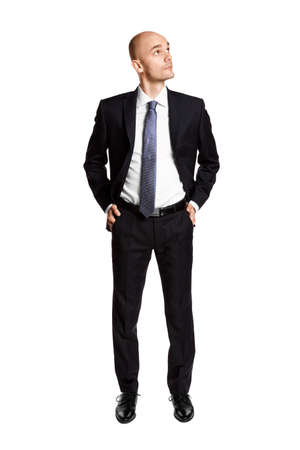 Full length portrait of young man looking left. Hands in pockets. Isolated on white.