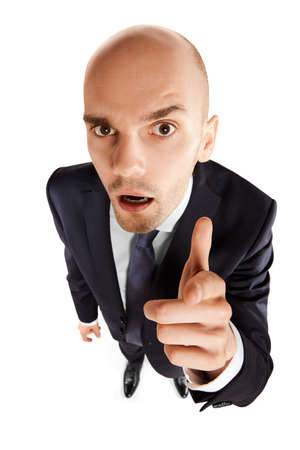 Above view of young businessman points his finger at you. Copy space. Isolated on white background.