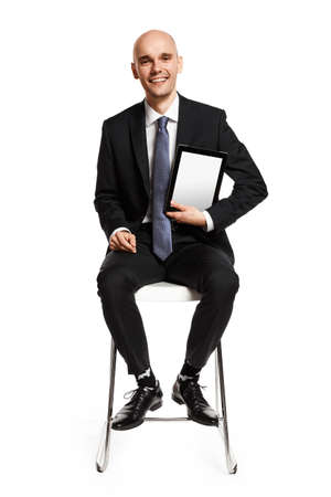Cheerful young businessman sitting on a chair and showing digital tablet. Isolated on white background. Stock Photo