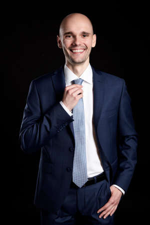 Young smiling businessman holding his tie. Portrait on black background.