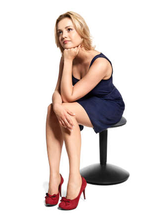 Portrait of pensive beautiful young woman sitting on stool and looking away. Studio shot. Isolated on white.