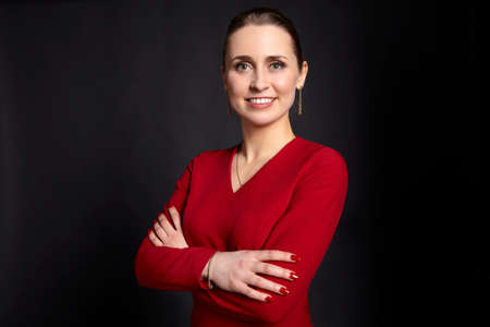 Studio shot of confident young business woman with crossed arms and toothy smile on black background.