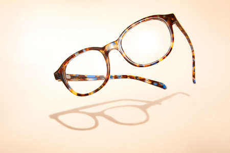 Advertising photo of flying glasses with shadow on beige background. Stock fotó
