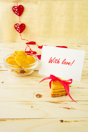 Card with Message With Love in the Letter and Cookies in the Shape of Heart at Valentine Day photo