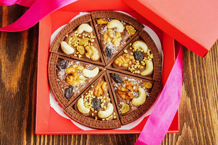 Chocolate pizza in gift box on wooden background photo
