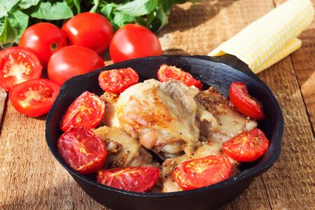 piri piri: Mustard glazed chicken thighs with garlic and tomatoes on the rustic wooden table Stock Photo