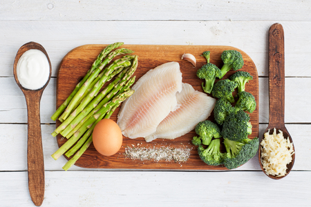 生イズミダイの魚、卵、アスパラガス、ブロッコリー、クリーム、ガーリック、木製のテーブルの上に塩。魚料理の準備です。選択と集中、トップ