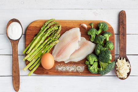 Raw tilapia fish, egg, asparagus, broccoli, cream, garlic, salt on wooden table. Fish dish preparation. Selective focus, top view