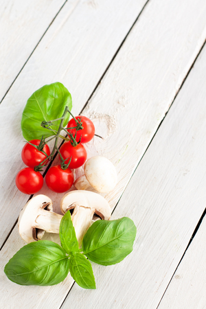 champignons: Sliced champignons, cherry tomatoes and basil on white wooden background with copyspace Stock Photo