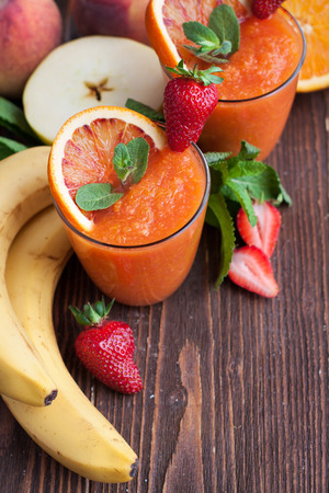 Freshly blended fruit smoothies. Summer drink with ingredients (apple, banana, strawberry, orange, mint) on dark wooden table
