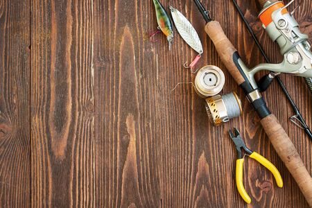 Fishing tackle - fishing spinning, fishing line, hooks and lures on wooden background