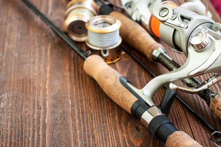 Fishing gear - fishing spinning, fishing line, hooks and lures on wooden background Stock Photo