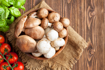 Fresh mushrooms, cherry tomatoes and basil on wooden background Stock Photo