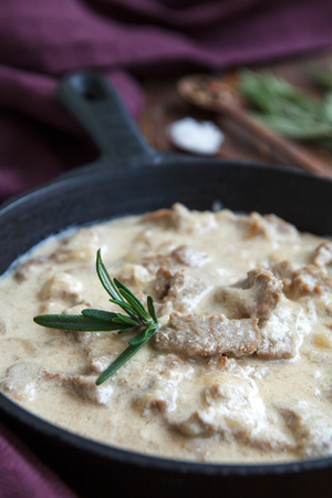 Meat stew with cream sauce and herbs on old wooden table Stock Photo