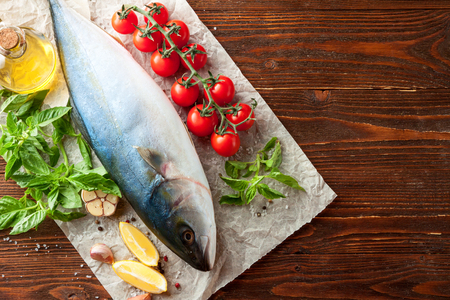 Whole fresh tuna with �herry tomatoes, lemon, basil, garlic and spices on baking paper on wooden background Banque d'images