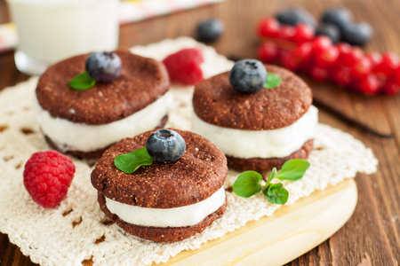 Chocolate sandwich cookies with cream of whipped egg whites adorned with berries and mint leaves Foto de archivo