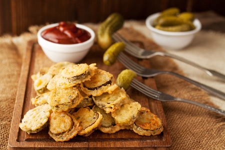 Battered fried pickles with ketchup dipping sauce on wooden board