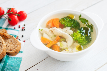 Chicken detox soup with carrots, broccoli, celery, onion and herbs on white wooden table