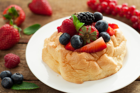 Stunningly beautiful and delicious Pavlova cake with fresh berries on wooden background